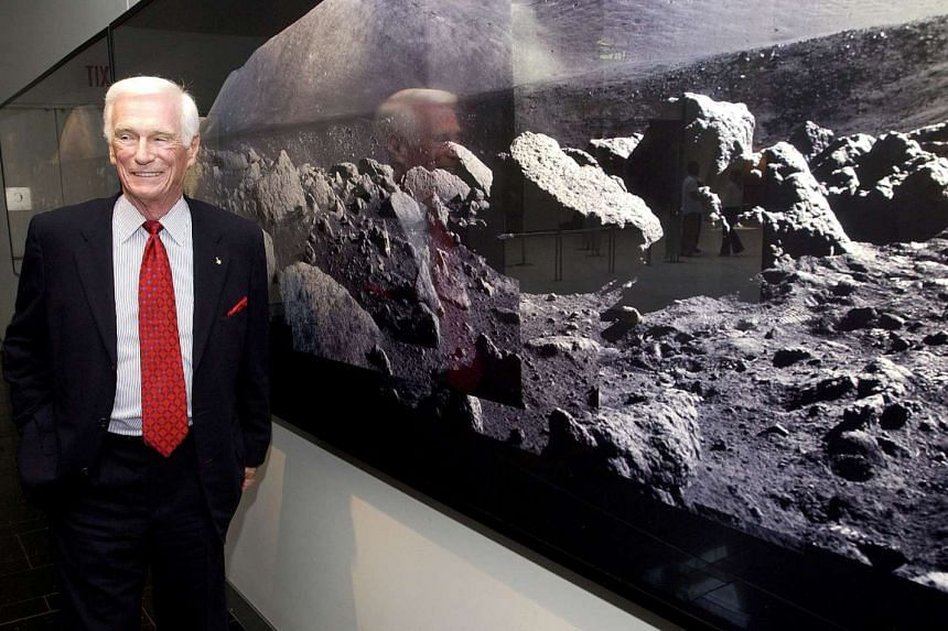 Former astronaut Gene Cernan, the last man to walk on the moon, standing next to a wall of photographs he made on the Apollo 17 mission, at the Museum of Natural History in New York, on May 7, 2004.