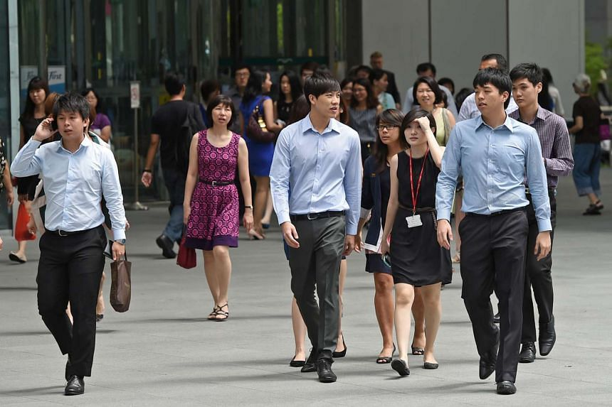 Office workers walking outside Raffles Place MRT station during lunch time.