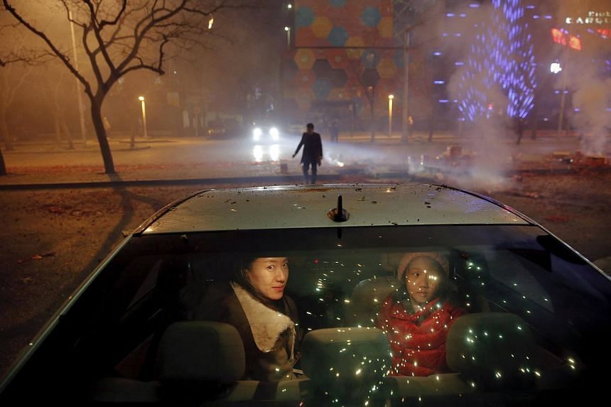 A girl and a woman sitting inside the car as firecrackers and fireworks explode celebrating the start of the Chinese Lunar New Year of Monkey in Beijing just before midnight, on Feb 7, 2016.