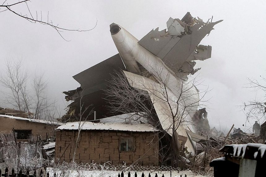 A big section of the aircraft (above) sticks out of a home at the crash site of a Turkish cargo jet near Kyrgyzstan's Manas airport, outside the capital Bishkek, yesterday. Rescue officials were seen recovering bodies at Dacha-Suu (below). At least 3