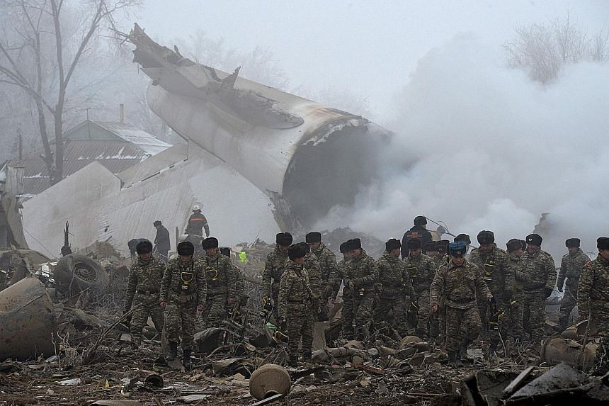 Rescuers going through the crash site of a Turkish cargo plane in the village of Dacha-Suu, outside the Kyrgyz capital of Bishkek, yesterday. At least 37 people, most of them residents of the village, were killed. A Boeing 747-400 from ACT Airlines,