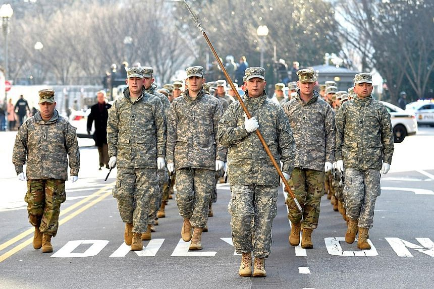 Above: Members of the US military practise marching for Friday's inauguration parade in Pennsylvania Avenue near the White House. Left: Street posters calling for protests are seen in the Dupont Circle area of Washington.