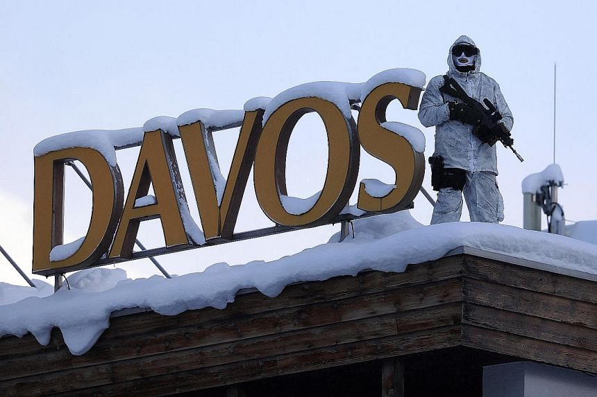 An armed member of the Swiss Police standing guard on the roof of the Hotel Davos yesterday, ahead of the World Economic Forum in Davos, Switzerland. The annual conference to seek solutions to society's biggest problems will hold its discussions this