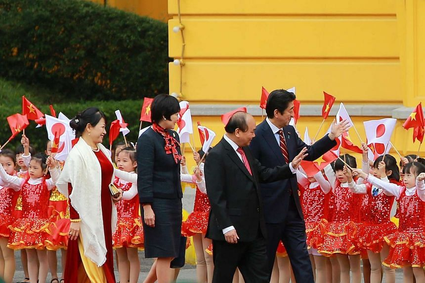 PM Shinzo Abe (right) and his wife Akie (in black) visiting the Presidential Palace in Hanoi yesterday, accompanied by Vietnamese Prime Minister Nguyen Xuan Phuc and his wife Tran Nguyen Thu. Mr Abe's trip to Vietnam ends today.