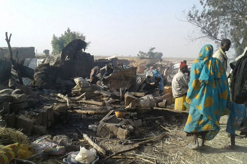 People walk past the site of an air strike that hit an internally displaced persons camp in Rann, Nigeria, on Jan 17, 2017.