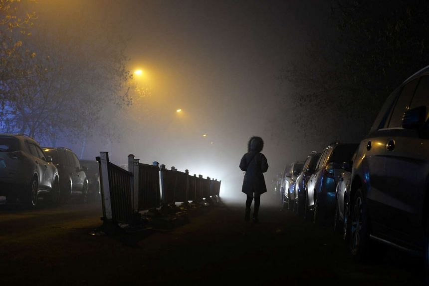 A woman walks past parked cars in heavy smog in Urumqi, Xinjiang Uighur Autonomous Region, China on Jan 7, 2017.