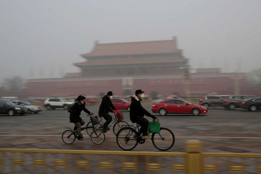 People wearing masks cycle past Tiananmen Gate during the smog after a red alert was issued for heavy air pollution in Beijing, China.