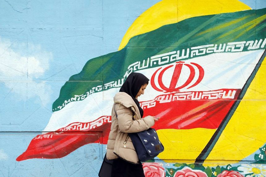 An Iranian woman walk next to a painting of Iran's national flag in a street in Tehran, Iran, on Jan 15, 2017, on the first anniversary of nuclear deal between Iran and world powers.