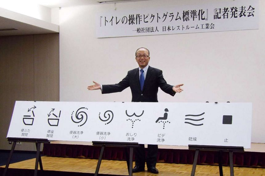 Madoka Kitamura, chairman of the Japan Sanitary Equipment Industry Association, showing off unified signs for high-tech toilet functions in Tokyo on Jan 17, 2017.