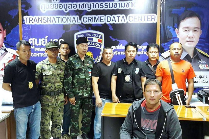 Zdenek Pfeifer (front, right) sitting in front of Thai police officers after he was arrested on Jan 17, 2017.