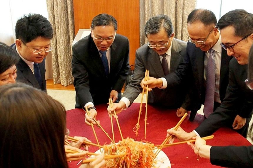 "Diplomats from Singapore and China doing the traditional ""prosperity toss"" of yusheng at lunch yesterday, ahead of the Chinese New Year."