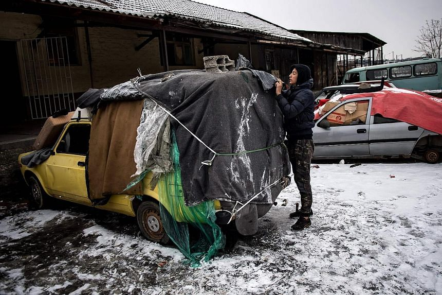 A migrant covering an abandoned car he uses as a makeshift shelter near Belgrade's main railway station yesterday, as temperatures plummeted drastically below 0 deg C. According to the latest figures, around 7,000 migrants are stranded in Serbia.