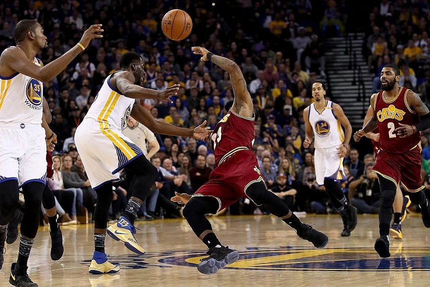 Draymond Green (left) harassed LeBron James (centre) all game, as the Warriors held the Cavs to 35.2 per cent from the field.