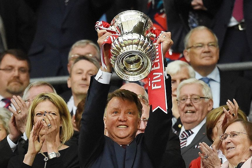 Former Man United manager Louis van Gaal lifting the FA Cup last year, despite an unsuccessful spell at the club.