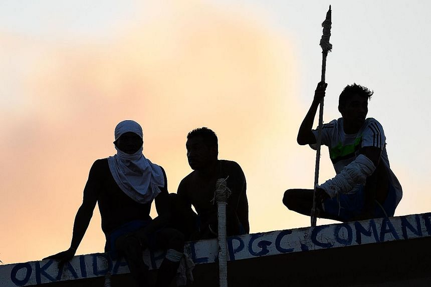 Prisoners atop the roof of a compound celebrating the transfer of their leaders after a negotiation with the police at the Alcacuz Penitentiary, in Rio Grande do Norte, on Monday. On Sunday, the police stormed the prison and ended a night-long riot.