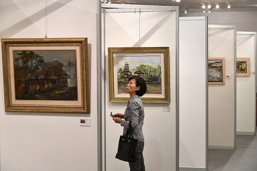 Madam Sharon Chow, a housewife in her 40s, looking at oil paintings at an exhibition by artist and retired art teacher Tan Choo Kai yesterday evening. Tapestry Of Nature, Mr Tan's latest solo exhibition, features 99 oil paintings and was launched yes