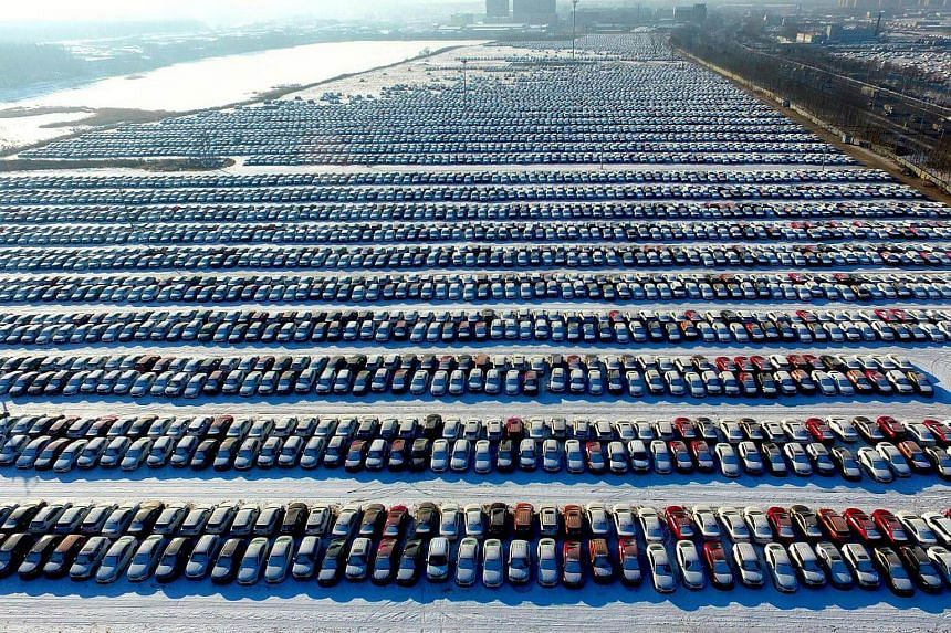 This aerial photo taken on Jan 16, 2017 shows new cars lined up at a parking lot in Shenyang, northeast China's Liaoning province.