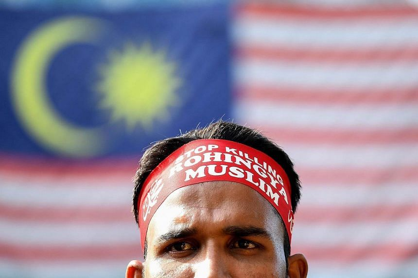 An Ethnic Rohingya Muslim refugee stands infront of the Malaysian flag during a gathering in Kuala Lumpur on Dec 4, 2016.