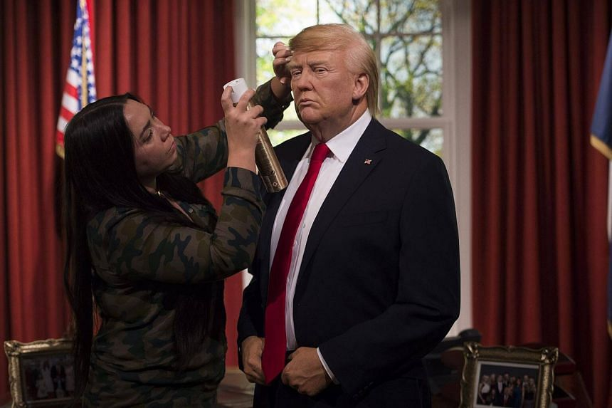 Madame Tussaud designers adjust a wax figure of US President-elect Donald Trump as its unveiled at Madame Tussauds in Central London, Britain.
