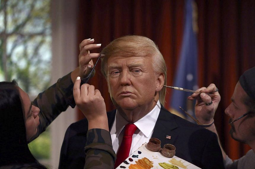 Gallery assistants pose, pretending to put the finishing touches to the hair and make-up of a waxwork of US President-elect Donald Trump, during a media event at Madame Tussauds in London, Britain.