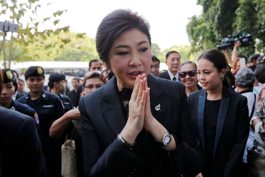 Ousted former Thai Prime Minister Yingluck Shinawatra greets supporters as she arrives at the Supreme Court for a trial on criminal negligence over a rice-buying scheme, in Bangkok on Dec 14, 2016.