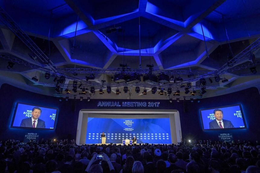 China's President Xi Jinping (left) delivers a speech during the first day of the World Economic Forum, on Jan 17, 2017 in Davos.