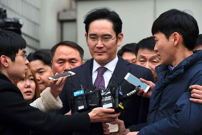 Samsung Group heir-apparent Lee Jae-Yong (centre) leaves for a waiting facility after attending a court hearing on whether he will be issued with an arrest warrant on Jan 18, 2017.