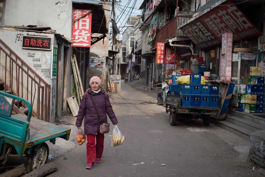 A woman walks on a street with her groceries in Beijing on Jan 18, 2017.