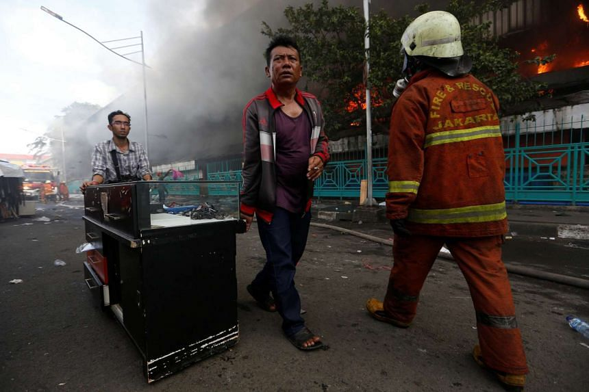 People moving their belongings during a fire at the Pasar Senen market in Jakarta on Jan 19, 2017.