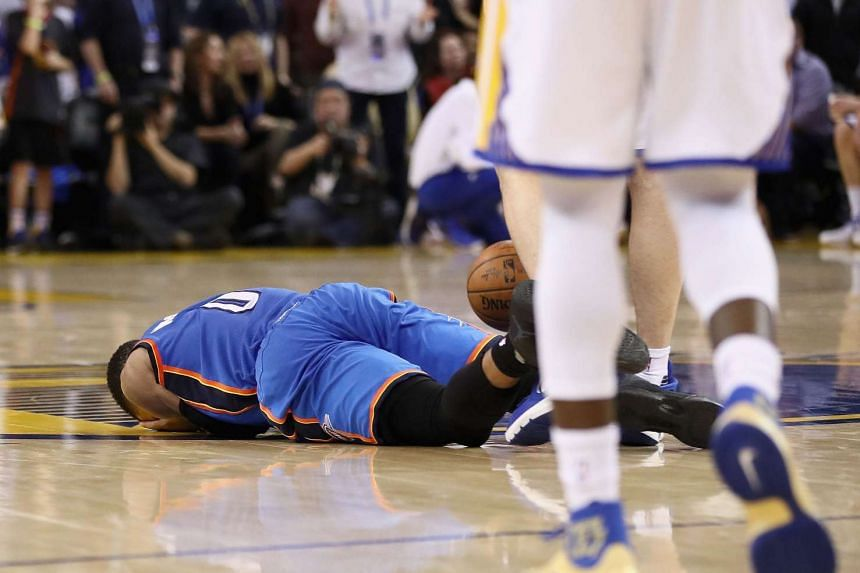 Oklahoma City Thunder guard Russell Westbrook lies on the ground after being fouled by Golden State Warriors centre Zaza Pachulia, during their NBA game on Jan 18, 2017.