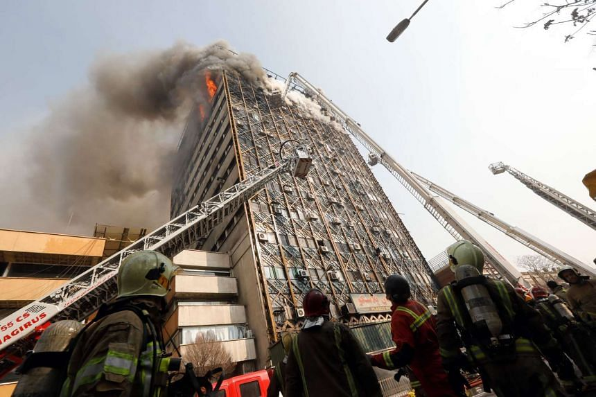 Firefighters battle a blaze that engulfed Iran's oldest high-rise, the 15-storey Plasco building in downtown Tehran on Jan 19, 2017.