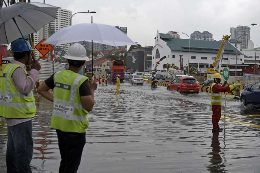 Workers from a nearby construction site stand along the road to direct traffic away from the water during a flash flood at the intersection between Upper Thomson Road and Thomson Ridge on Jan 19, 2017.