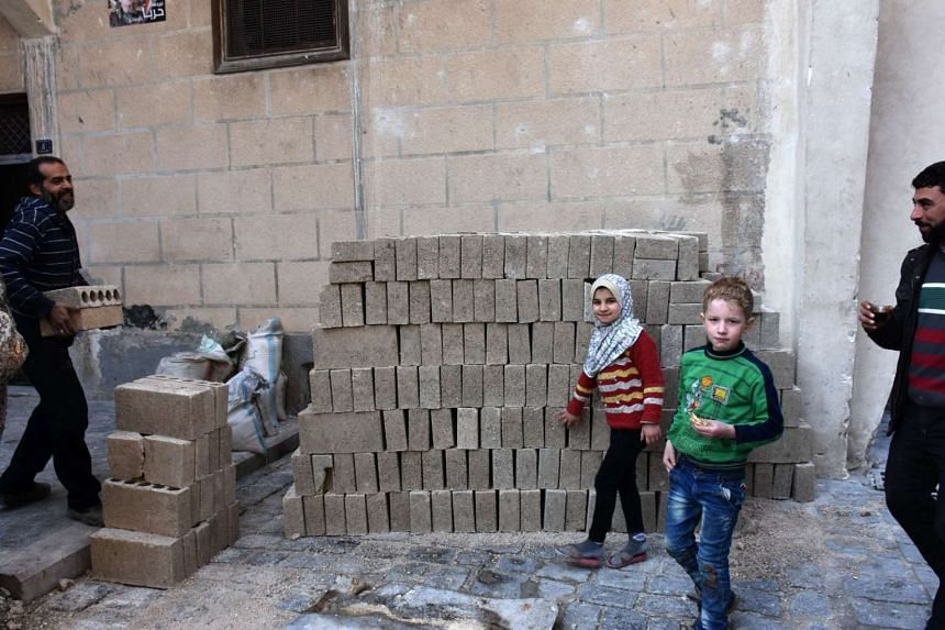 Syrian children look on as a man stacks bricks in Aleppo's old city on Jan 19, 2017, a month after government forces retook the northern Syrian city from rebel fighters.