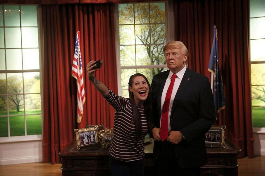 A woman poses with a waxwork of US President-elect Donald Trump during a media event at Madame Tussauds in London, Britain.