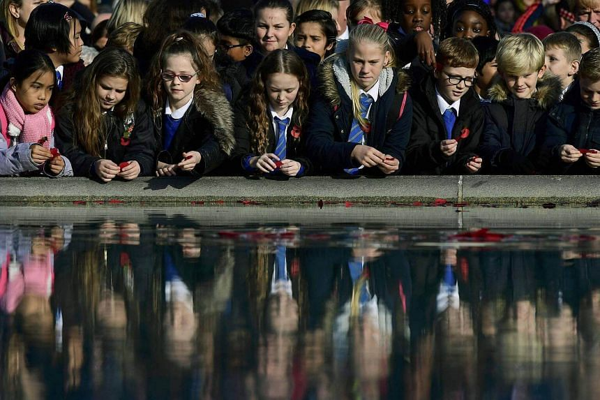 School children throw poppies into a fountain during an Armistice Day event at Trafalgar Square in London.