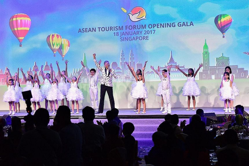 Composer Dick Lee performing the song Rise with children from the Kids Performing Academy of the Arts at the Asean Tourism Forum yesterday. The Visit Asean@50 campaign coincides with Asean's 50th anniversary and will feature the region's 50 best fest