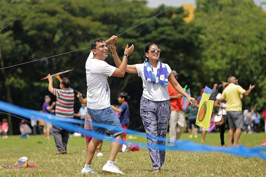 Mr Nilang Shah, 41, flying a kite with his wife Tasneem Shah, 40, at West Coast Park on Sunday, during the Singapore Gujarati Society's celebration of Utraan, the Gujarati kite-flying festival. An 1886 Straits Settlements bank note from HSBC, which f