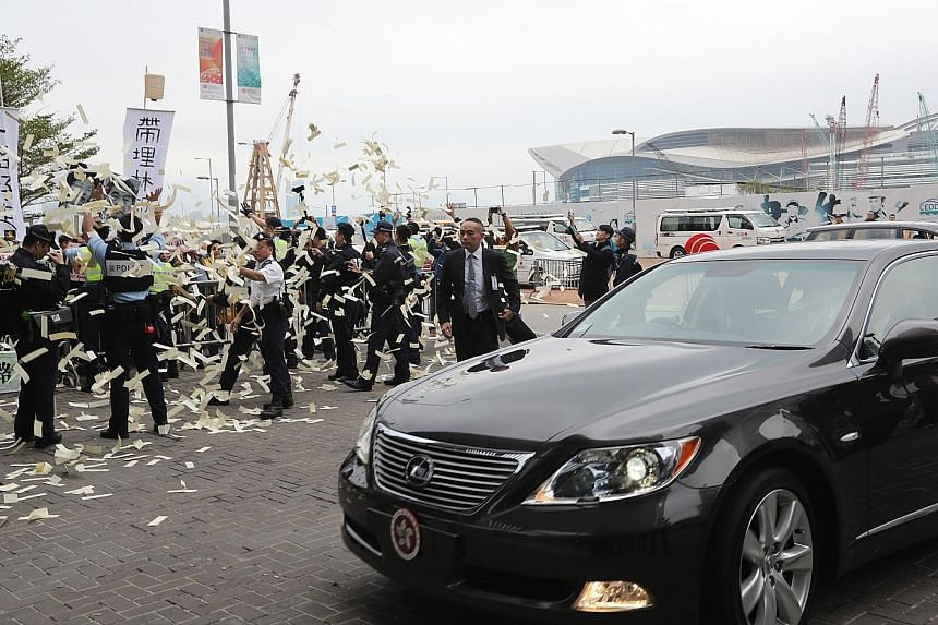Protesters throwing hell money at Chief Executive Leung as his car arrived at Hong Kong's Legislative Council yesterday. Mr Leung will be stepping down from his post in less than six months.
