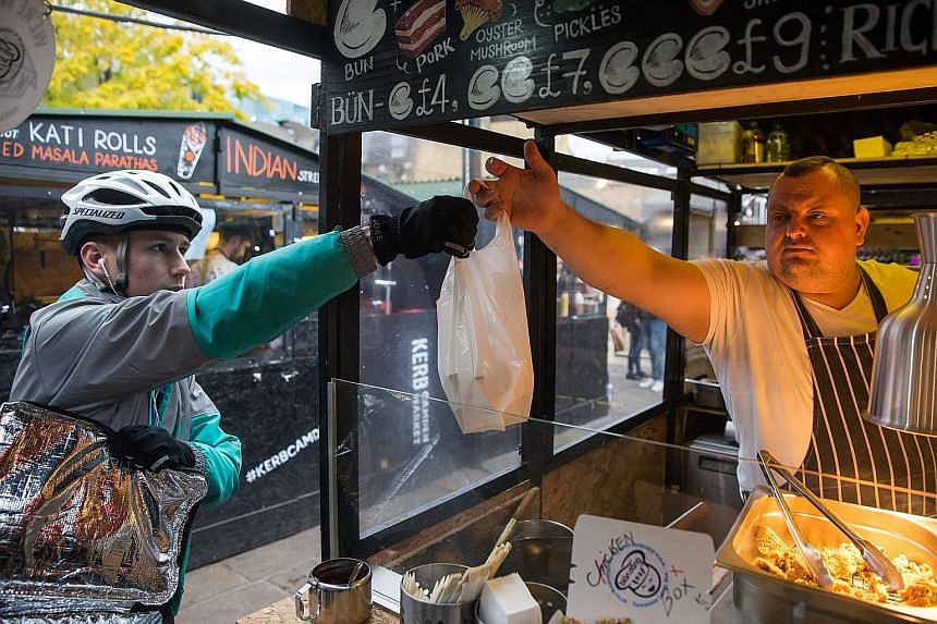 A Deliveroo employee picks up an order from an eatery in Camden Town in north London. Deliveroo's plan to hire more technology workers will expand its presence in London.