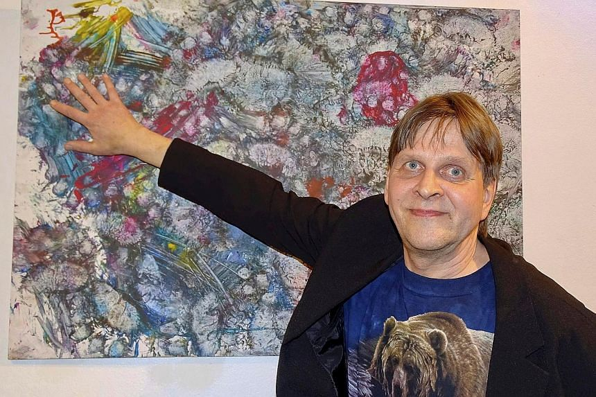 Mr Pasi Jantti, a keeper of a bear called Juuso, pointing to a painting done by the bear at a gallery in Helsinki, Finland. Juuso, an orphaned brown bear from Lapland, uses its body as a paint brush to generate artwork. The money raised is being used
