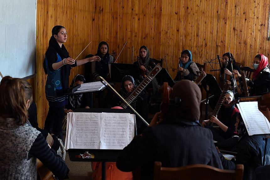 Afghanistan's first all-female orchestra, led by Ms Khpalwak (left), rehearsing at the country's National Institute of Music in Kabul earlier this month. They have overcome death threats and discrimination to play together, and will be performing bef