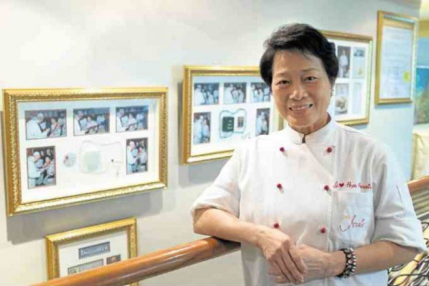 Chef Jessie Sincioco standing next to a display in her restaurant showing memorabilia of Pope Francis' visit to the Philippines in 2015.
