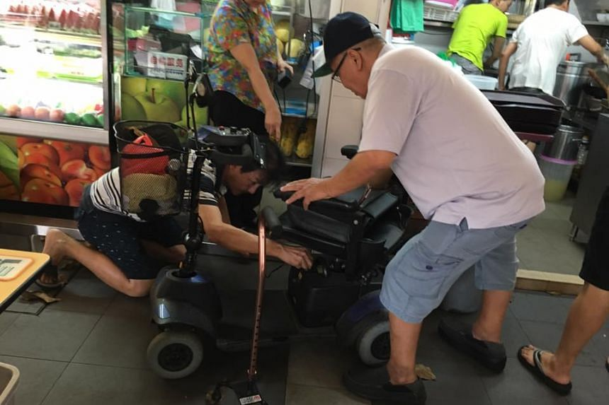 People at Bukit Merah View Hawker Centre helping a man known as Uncle Sim after his motorised wheelchair stalled, on Jan 15, 2017.