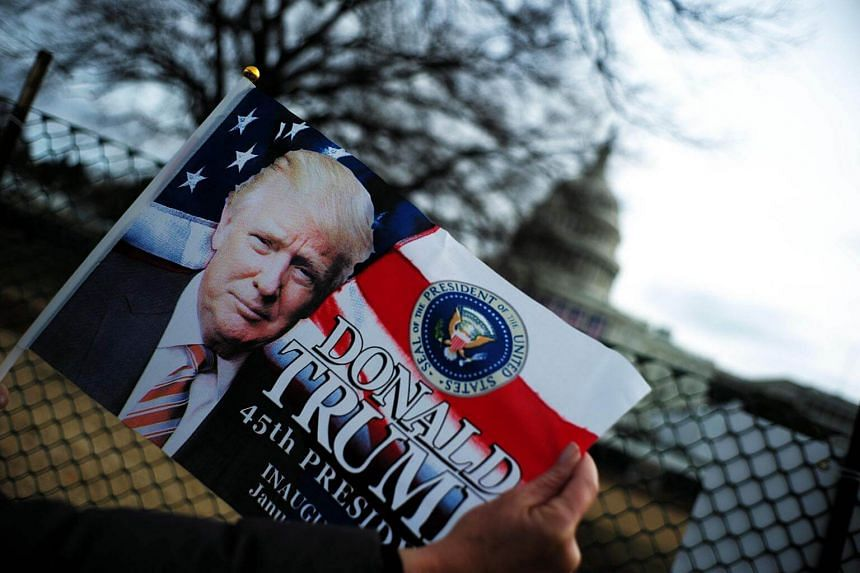 Third-grade school teacher Kimi Moro poses with a flag featuring a picture of US President-elect Donald Trump near the Capitol Building in Washington, DC.