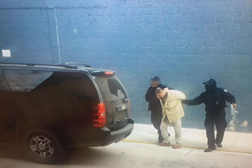 """Joaquin """"El Chapo"""" Guzman being escorted by Mexican police as he is extradited to the United States on Jan 19, 2017."""