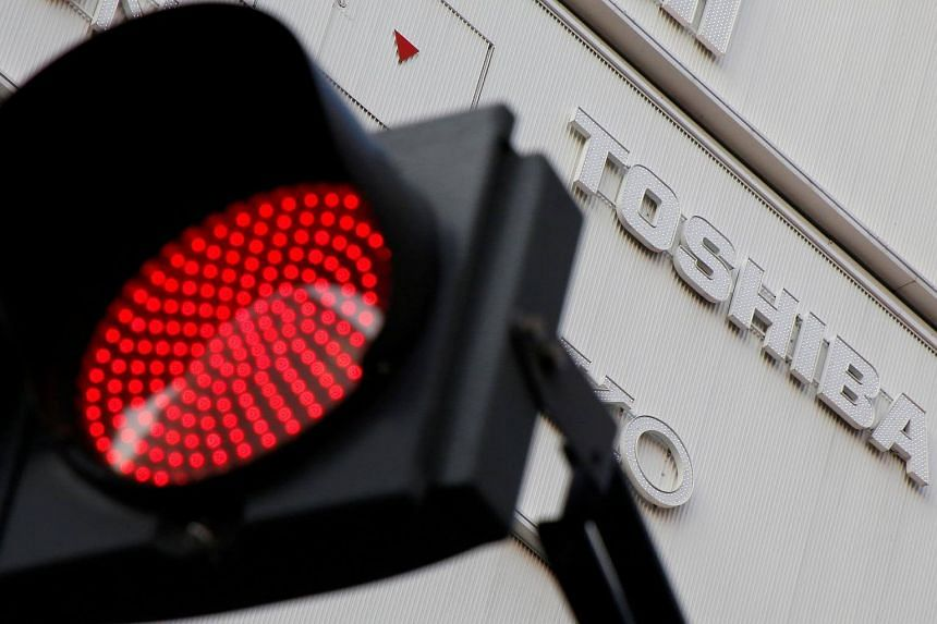 A logo of Toshiba Corp is seen behind a red light signal outside an electronics retail store in Tokyo, Japan on Jan 19, 2017.