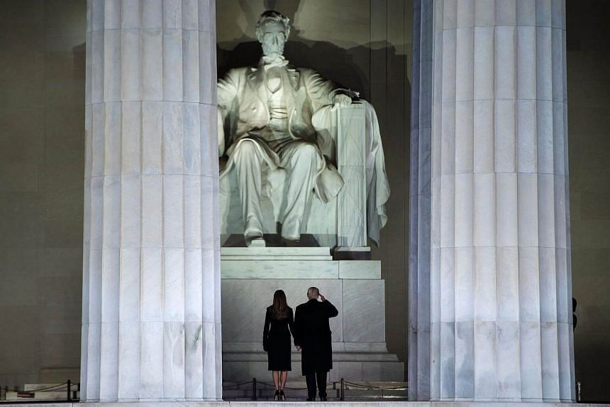 US President-elect Donald Trump and wife Melania look at the Abraham Lincoln statue as they arrive for a welcome celebration at the Lincoln Memorial in Washington, DC, on Jan 19, 2017.