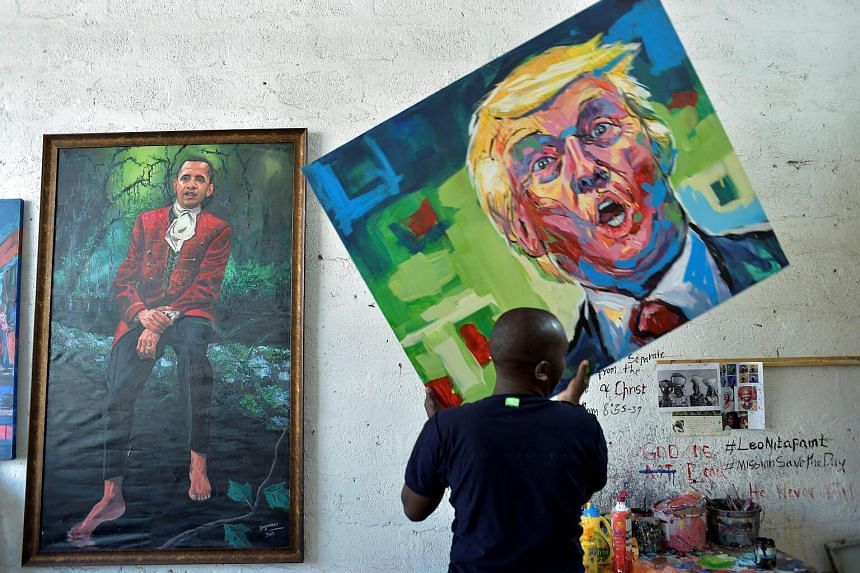 Kenyan artist Evans Yegon carrying one of his painting of US President-elect Donald Trump past the current President Barack Obama at his workshop.
