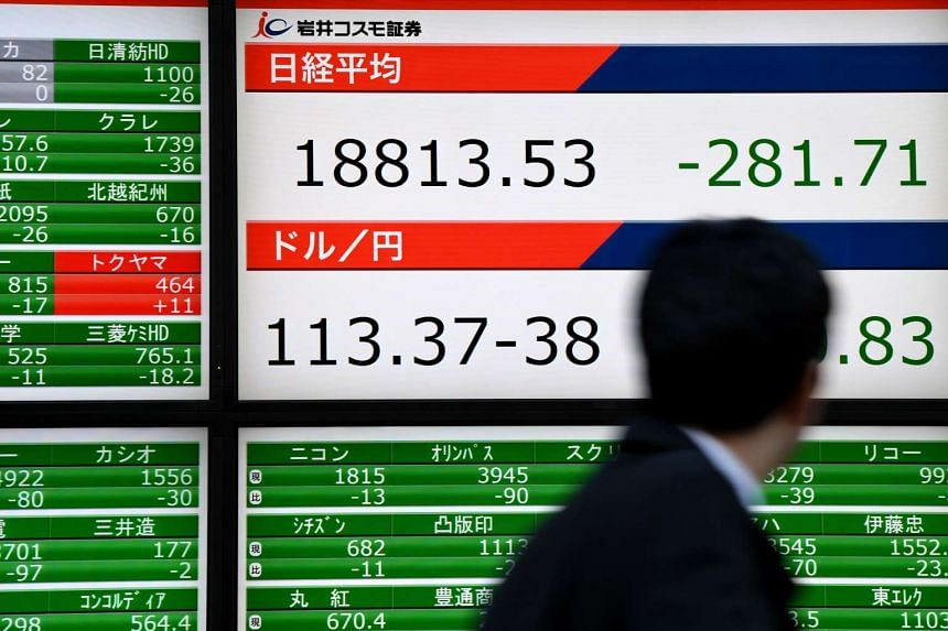 A businessman looks at the stock and forex indicators at the window of a security company in Tokyo, Japan.