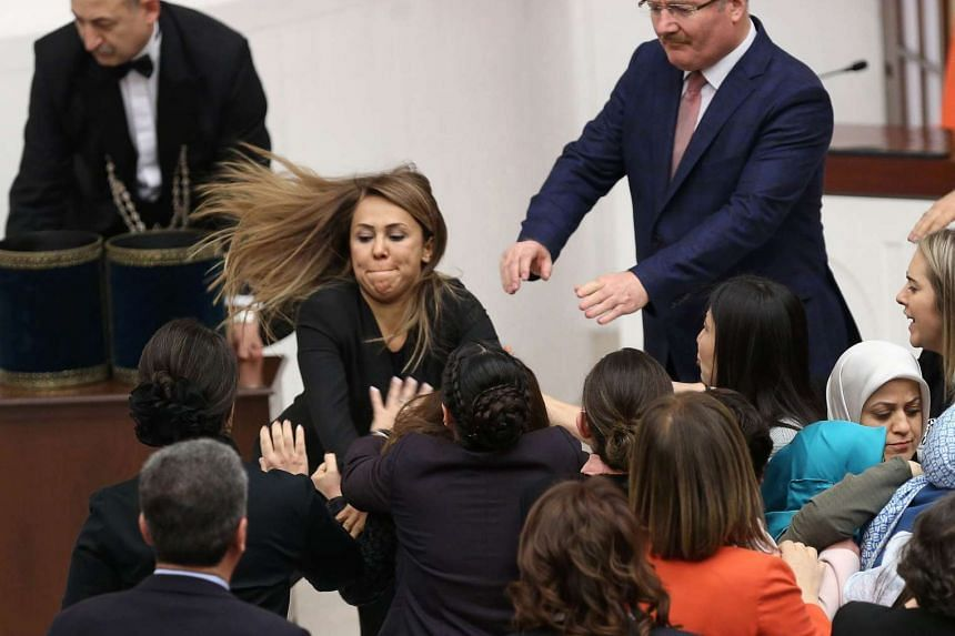 Ruling AK Party and opposition lawmakers scuffle after Turkish deputy Aylin Nazliaka had handcuffed herself to the podium in a protest against the constitutional reform aimed at strengthening the powers of the Turkish president during a debate at the